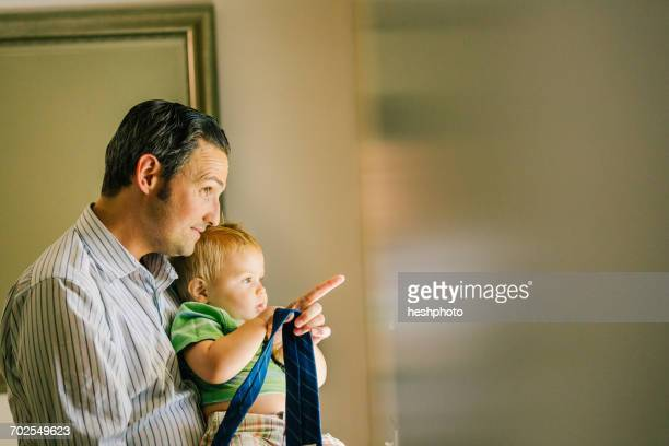 father holding young son, looking out of window - heshphoto stockfoto's en -beelden
