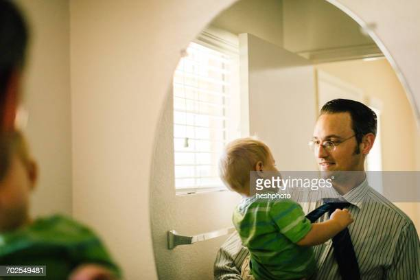 father holding young son, reflected in mirror - heshphoto stockfoto's en -beelden
