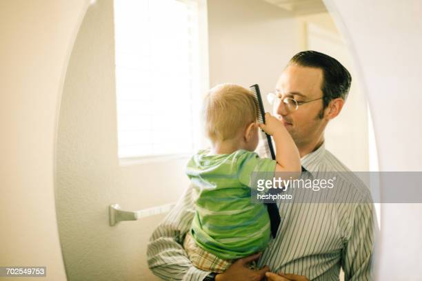 father holding young son, son combing hair, reflected in mirror - heshphoto stockfoto's en -beelden