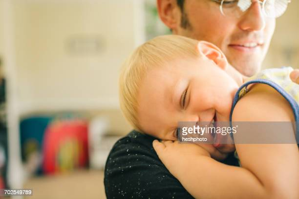 father holding young son, son laughing, mid section - heshphoto stockfoto's en -beelden