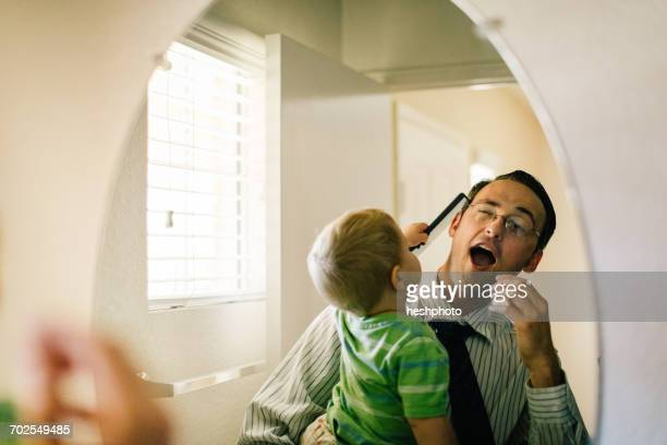 father holding young son, son trying to comb fathers hair, reflected in mirror - neonati maschi foto e immagini stock