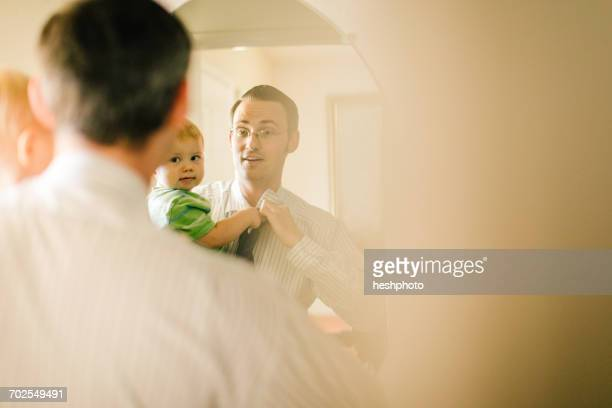 father holding young son, whilst getting dressed, looking in mirror - heshphoto stock pictures, royalty-free photos & images