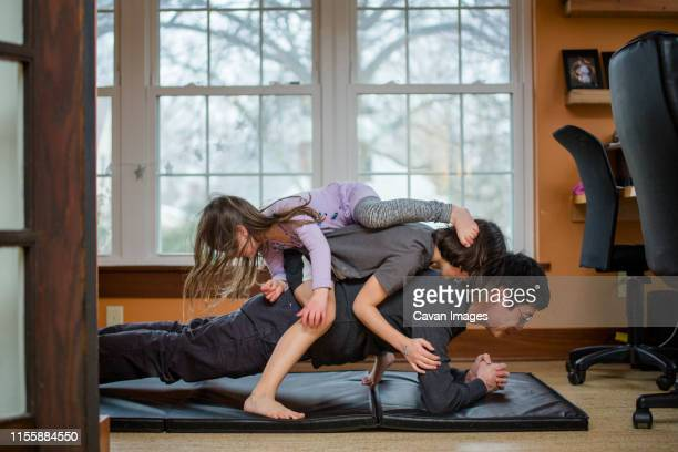 a father holds a plank position with two children piled on his back - exercise at home stock pictures, royalty-free photos & images