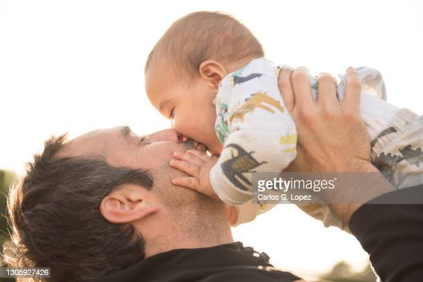 a father holds his baby boy up in the air and kisses him in a public play park in a sunny day - genderblend stock pictures, royalty-free photos & images