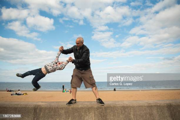 a father holds his child's hands and swings him side to side near a beach - bright colour stock pictures, royalty-free photos & images