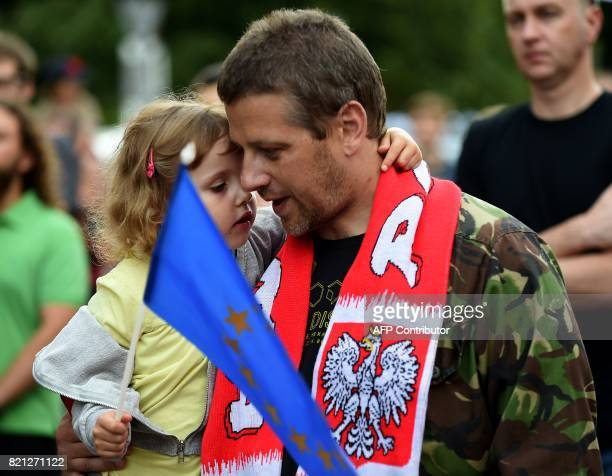 A father holds his daughter as she waves the European union flag during a protest in front of the presidential palace in Warsaw as they urge Polish...