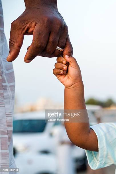 A father holds his daughters hand on the way to a traditional bull fight.