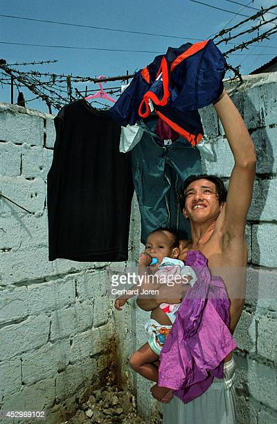 A father holds his son whilst putting his laundry out to dry at the cell block for Batang City Jail Gang one of four gangs at Manila City Jail Over...