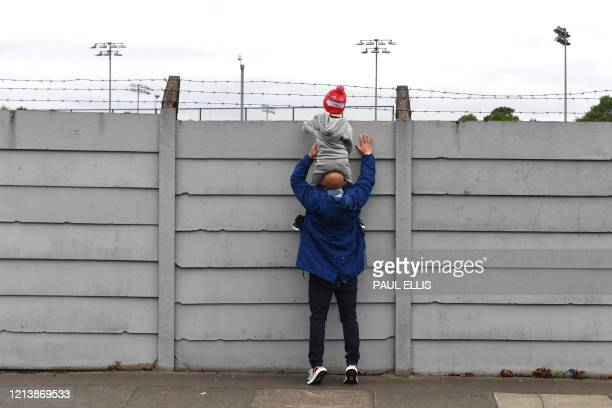 TOPSHOT A father holds up his son to look over the fence at Melwood training ground in Liverpool north west England as Liverpool players resume...