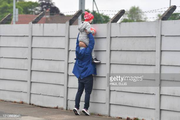 A father holds up his son to look over the fence at Melwood training ground in Liverpool north west England as Liverpool players resume training on...