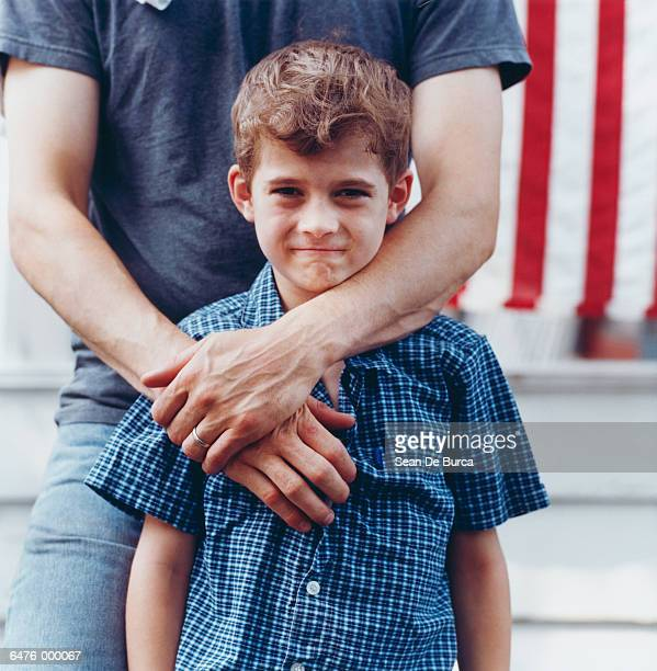 father hugging boy - kin in de hand stock pictures, royalty-free photos & images