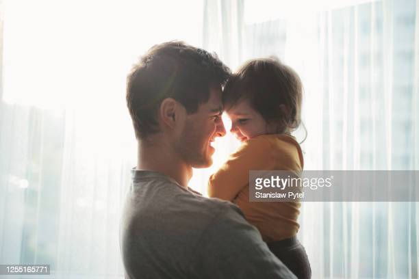 father hugging daughter and smiling against window - シングルファザー ストックフォトと画像