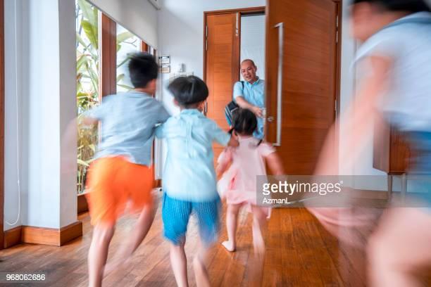 father hugging his children when coming home - seguir atividade móvel imagens e fotografias de stock