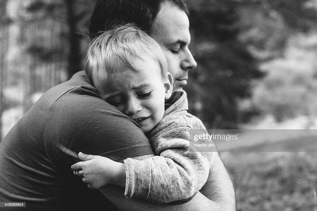 Father hugging his crying son : Stock Photo