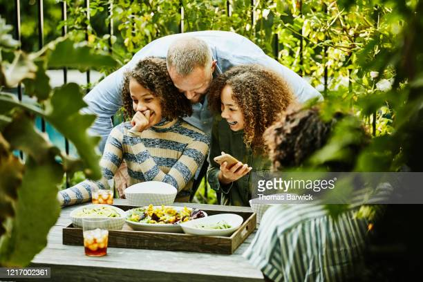 father hugging laughing daughters during backyard picnic - femme entre deux hommes photos et images de collection