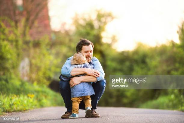 father hugging little boy on field path - innocence stock pictures, royalty-free photos & images