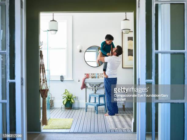 father hugging son in bathroom - domestic bathroom stock pictures, royalty-free photos & images