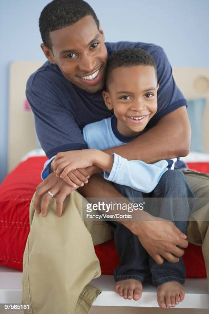 father hugging son - black men feet stock photos and pictures