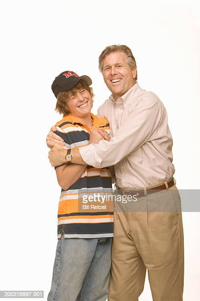 Father hugging teenage son (14-16), boy grimacing