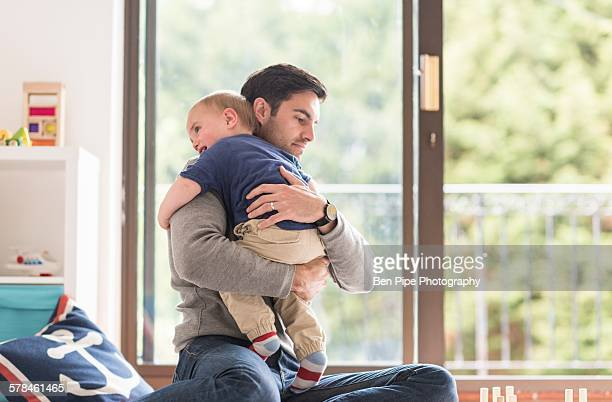 Father hugging young son, indoors