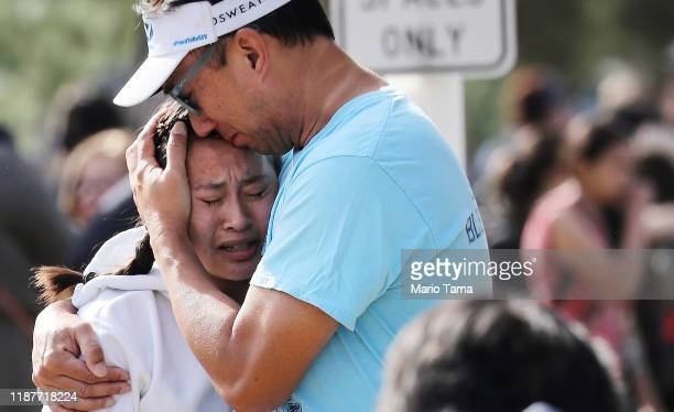 A father hugs his daughter after being reunited at a park near Saugus High School after a shooting at the school left two students dead and three...
