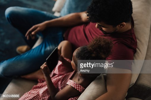 Father hugs his daughter while she's holding digital tablet