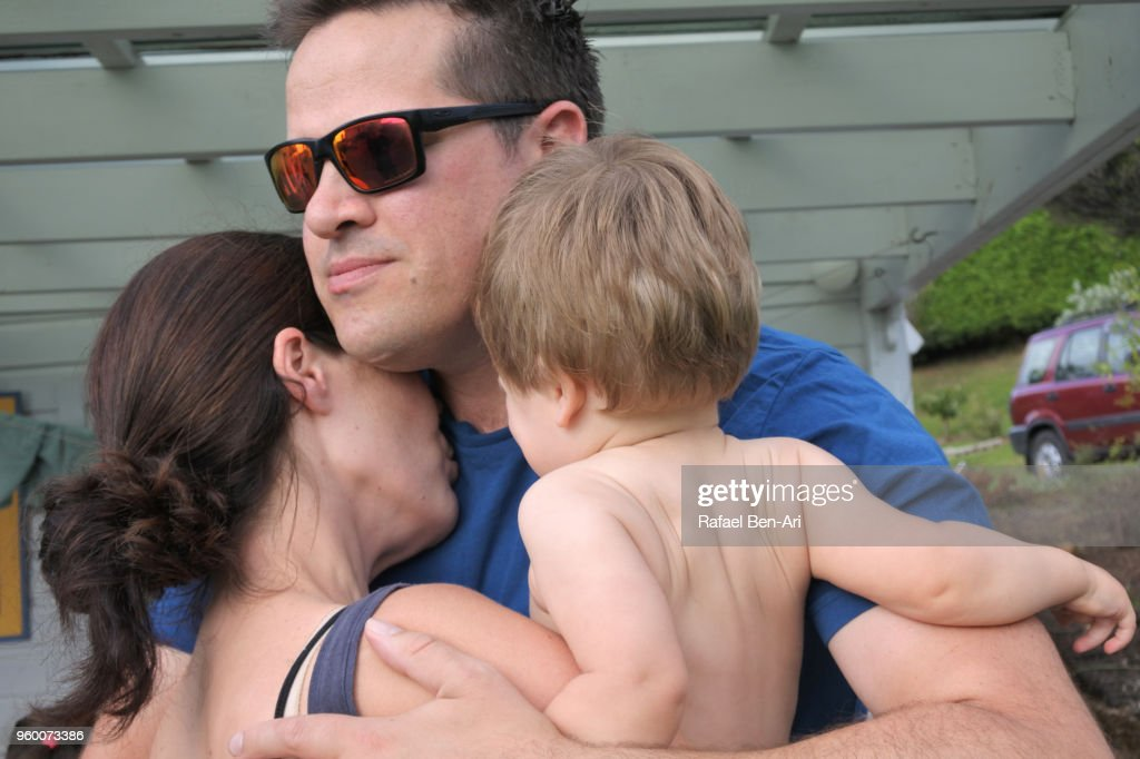Father hugs his wife and baby (age 01) before driving away from home : Stock-Foto