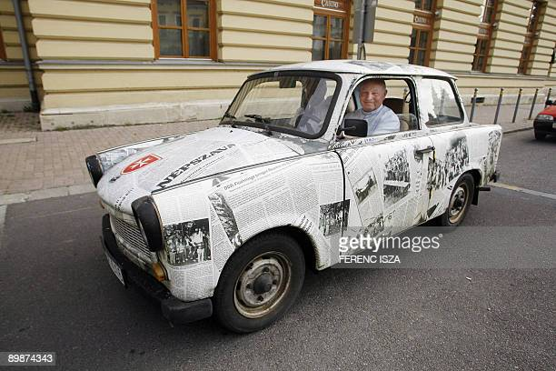 Father Imre Kozma head of Hungary's Maltese Charitable Service arrives in a Trabant decorated with reproductions of newspapers bearing stories of the...