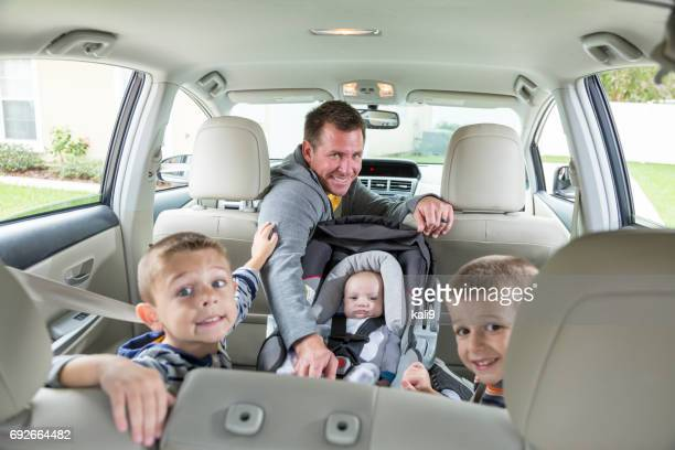Father in car with baby and two boys