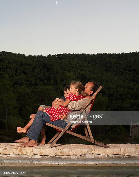 father in deckchair with son and daughter (6-7 years) in lap - 6 7 years stock pictures, royalty-free photos & images
