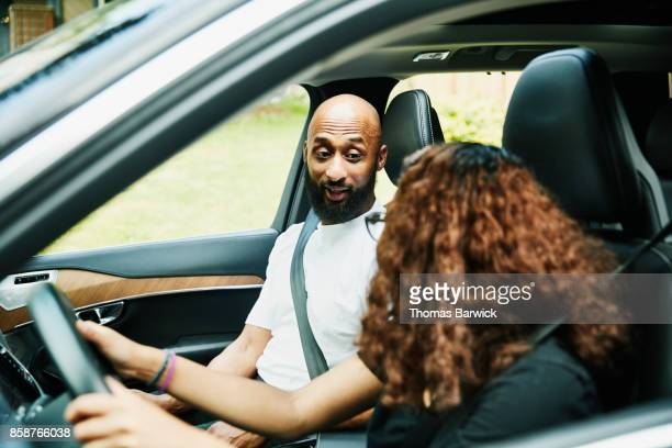 Father in discussion with daughter while teaching her to drive