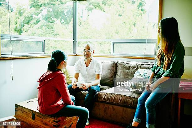 Father in discussion with daughters before school