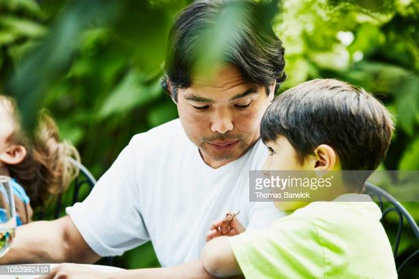 Father in discussion with son during backyard party