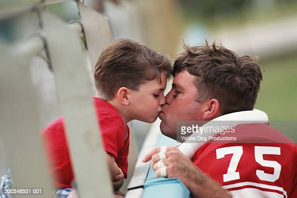 Father in football uniform kissing son (5-7) through picket fence