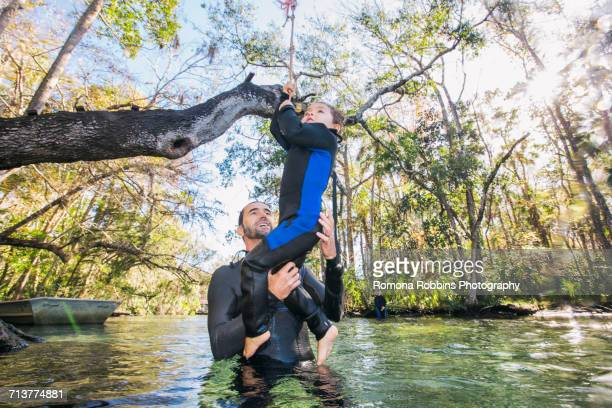 Father in river helping daughter with rope swing on tree, Chassahowitzka, Florida, USA
