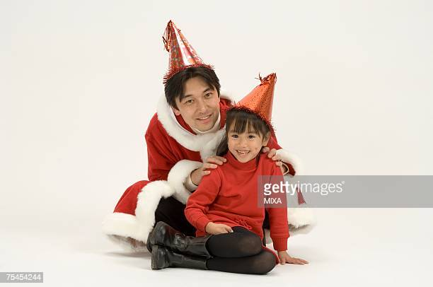 Father in Santa outfit sitting with daughter