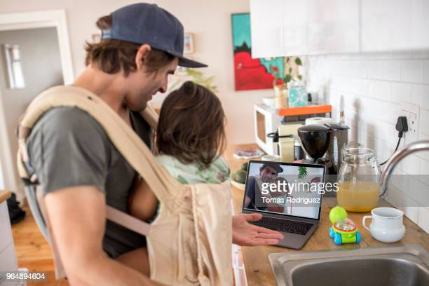 Father in the kitchen with a toddler in a baby carrier and a laptop