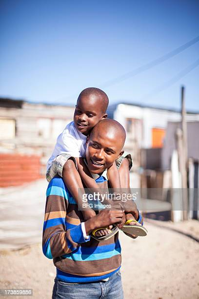 Father in Township with son on shoulders, Cape Town, South Africa