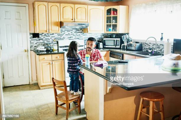 Father in wheelchair and daughter working together in kitchen to put away dishes