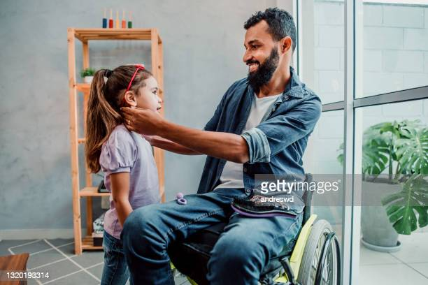 father in wheelchair fixing daughter's hair - genderblend stock pictures, royalty-free photos & images