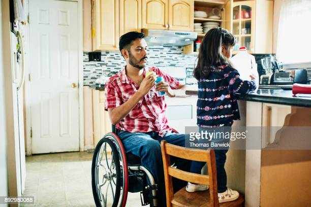 Father in wheelchair helping daughter make snack in kitchen