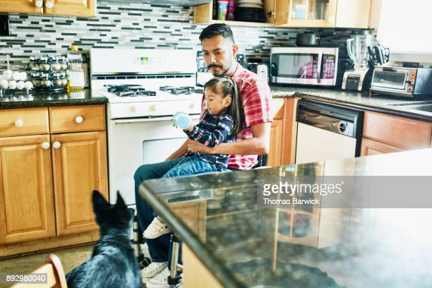 Father in wheelchair holding young daughter in lap while preparing snack in kitchen