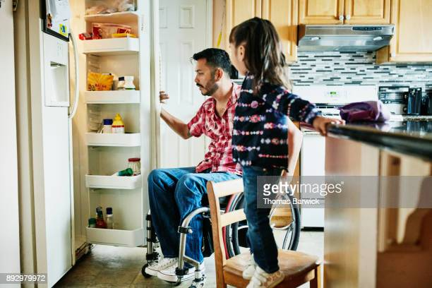 Father in wheelchair looking in refrigerator in kitchen while daughter stands on chair watching