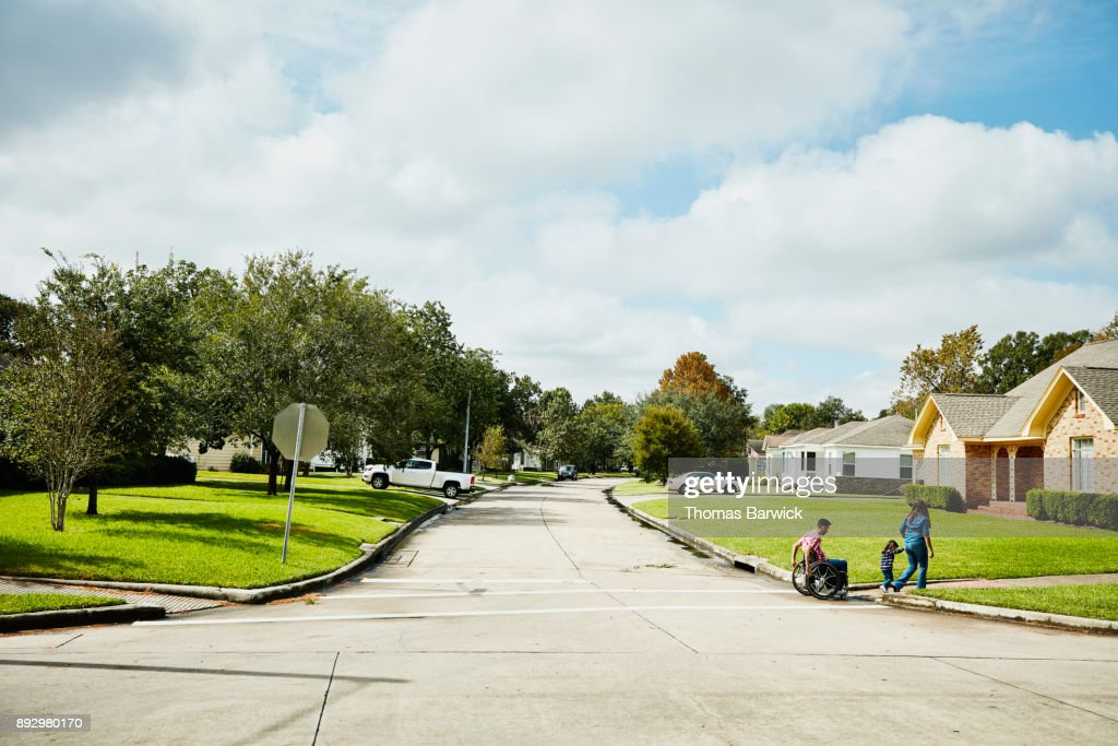 Father in wheelchair out for walk with wife and daughter on neighborhood street : Stock Photo
