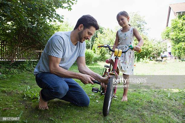 father inflating daughter's bicycle - air pump stock photos and pictures