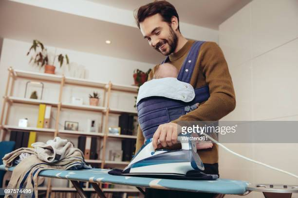Father ironing and carrying his baby at home