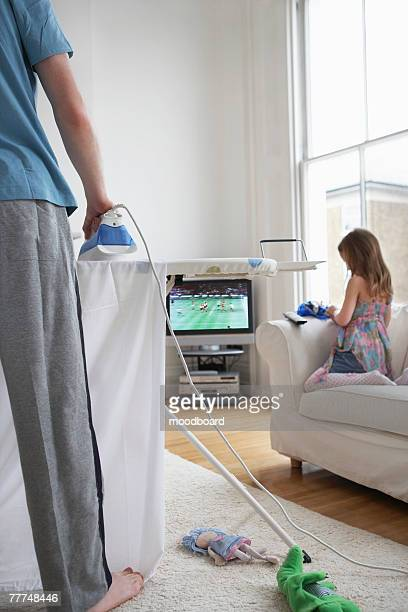 Father Ironing and Daughter Watching Television in Living Room
