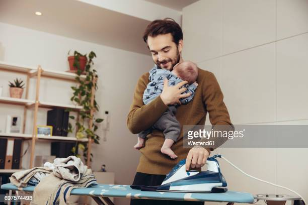 Father ironing and holding his baby at home