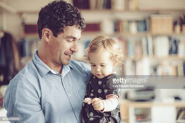 Father is holding his daughter