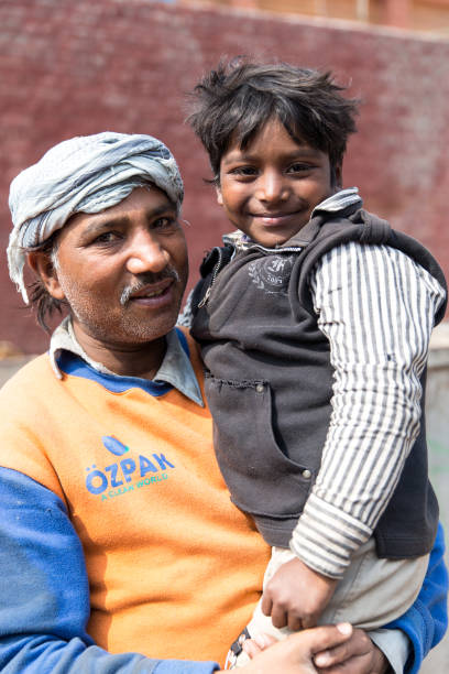 A father is holding his young boy in his arms on February 27 2014 in Lahore Pakistan A red brickwall can be seen in the background Lahore is the...